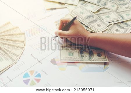 Business concept Hand holding ball pen pointing at summary reports and U.S. dollar bills on the table