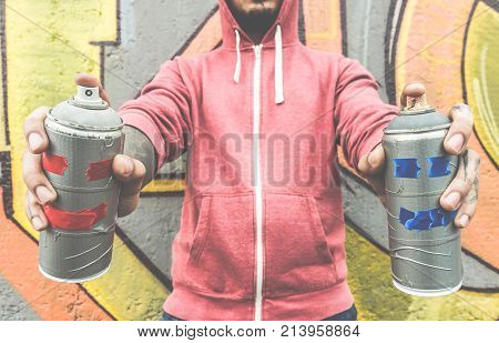 Young man drawing with two smiling sprays - Modern art concept with urban guy performing and preparing live murales with aerosol color spray - Focus on bottles spray - Contrast filter