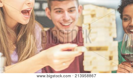 Group of young friends having fun playing board game at home - Diverse culture people laughing and enjoying time together at hostel - Friendship and youth concept - Focus on girl nose mouth