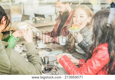 Happy friends eating breakfast and drinking coffee at bar restaurant - Trendy people having fun together - Friendship and morning break concept - Focus on woman eye - Window view