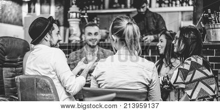 Trendy friends chatting and laughing together inside cocktail fashion bar - Cheerful people having fun doing pre dinner appetizer - Soft focus on left man face - Black and white editing
