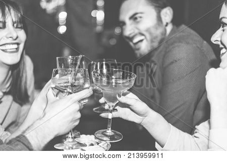Happy friends cheering at cocktail jazz bar - Young trendy people having fun drinking alcohol and laughing - Party concept - Focus on right woman hand glass - Black and white editing - Warm filter