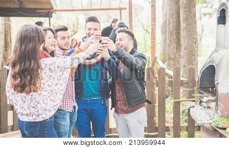 Happy friends cheering at barbecue dinner outdoor - Young people drinking red wine for bbq in garden backyard - Friendship and party concept - Focus on glasses - Warm vivid filter