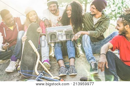 Happy students listening music and having fun in city park - Young friends enjoiyng time after university - Youth and friendship concept - Main focus on afro girl - Warm contrast filter