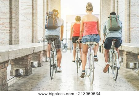 Happy friends riding city bikes in old town center - Young students having fun together going around with bicycles - Youth friendship and citylife concept - Focus on right woman body