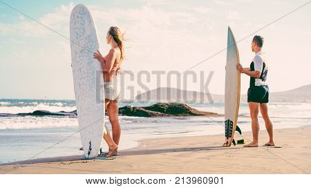 Surfers couple waiting for the high waves on beach - Sporty people with surf boards on the beach - Extreme sport and vacation concept - Focus on female body - Soft vintage filter