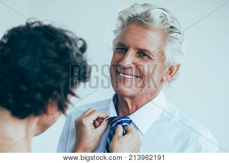 Careful wife tying tie to happy husband. Cheerful businessman looking at camera, he preparing for office work. Morning preparation or married life concept