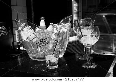 Key west Fl USA - March 30 2016: Schweppes Tonic Water bottles yellow color in glass with cold ice cubes on table near bocals of lemon beverage with drinking straw