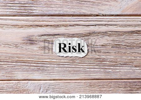 Risk of the word on paper. concept. Words of Risk on a wooden background.