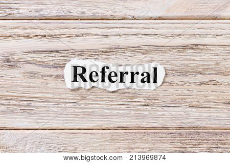 REFERRAL of the word on paper. concept. Words of REFERRAL on a wooden background.