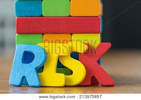 Risk concept with colorful wooden alphabets RISK and wooden blocks tower.