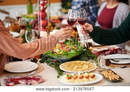 People clinking glasses with wine at Christmas dinner