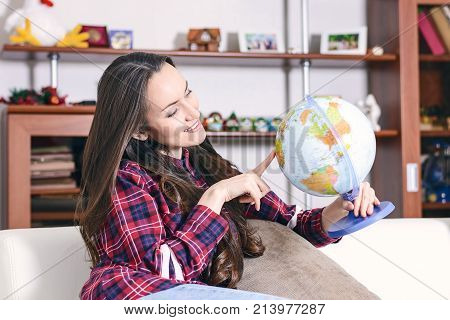 Go On An Adventure. Woman Dreaming About Traveling Around The World, Looking At The Globe In Room Of