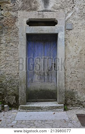 An old wooden door in a derelict building the historic hill village of Erto in Friuli Venezia Giulia north east Italy