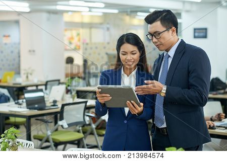 Asian businessman explaining information on tablet screen to female coworker