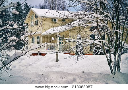 Beautiful suburban house surrounded by trees heavily covered with snow in january