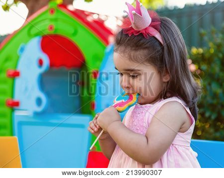 Baby toddler girl eating a large colorful lollipop dressed in pink dress as princess or queen with crown, playing outdoor in garden with playhouse