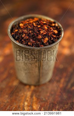chipotle jalapeno smoked chili flakes in vintage mould tin on textured woden background