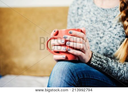 Woman With Beautiful Manicure Sitting And Holding A Pink Cup Of Tea Coffee