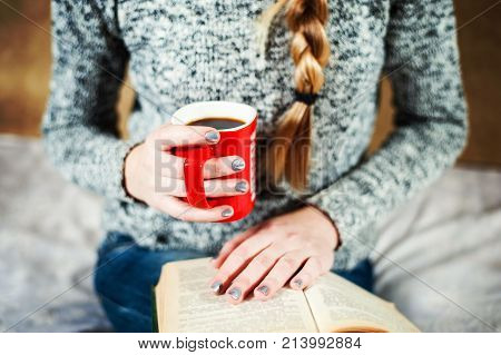 Young Girl In Jeans And Sweater Is Reading A Book With A Big Cup Of Coffeeor Tea.