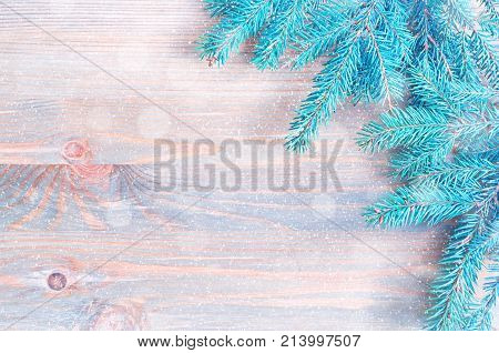 Winter background. Blue fir tree winter branches with snowflakes on the wooden background. Winter festive still life free space for text. Winter background with blue fir tree branches. Winter composition. Winter still life