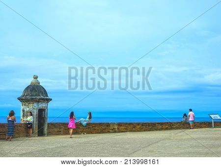 San Juan, Puerto Rico - May 08, 2016: The people making photos at large outer wall with sentry box of fort San Cristobal in San Juan, Puerto Rico on May 08, 2016