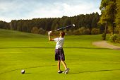 Boy golf player hitting by iron from fairway at golf course poster