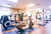 Blurred fitness center with cardio machines weight strength training equipment TV large mirror. Empty gymnasium facility service room in 3-star hotel in Texas USA. Active lifestyle. Vintage tone poster