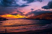 Sunset at Matala beach on Crete island, Greece. There is a girl walking on the beach. The colors in the sky are very beautiful yellow orange and red. poster