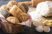 Basket with mixed buns and ingredients - Baking theme image with a wicker basket full of homemade bread rolls surrounded by flour eggshell butter and a rolling pin on a rustic wooden table. poster