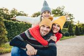 Horizontal portrait of family members spend free time together, embrace, encourage each other, have fun. Little smiling girl feels happiness, embrace her affectionate parents. Active lifestyle concept poster