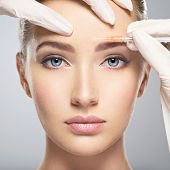 Portrait of young Caucasian woman getting botox cosmetic injection in forehead. Beautiful woman gets botox injection in her face. poster