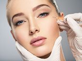 Woman getting cosmetic injection of botox in cheek, closeup. Woman in beauty salon. plastic surgery clinic. poster