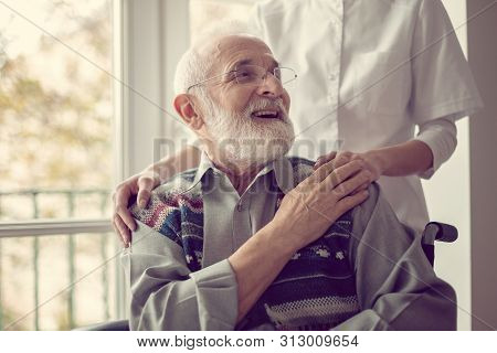 Senior Man Sitting On The Wheelchair, Laughing And Holding His Nurse's Hand