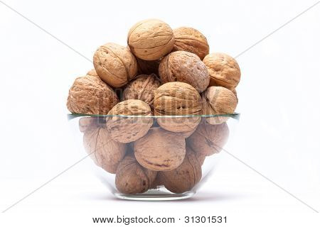 Walnuts lie in a glass bowl isolated on white