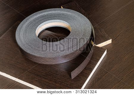 Roll melamine edge for finishing of furniture. Edging tape lying on laminated chipboard sheets wenge color. poster