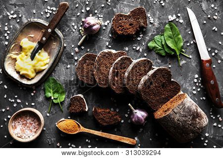 Sliced Bread With Butter And Pieces Scattered On A Dark Background A