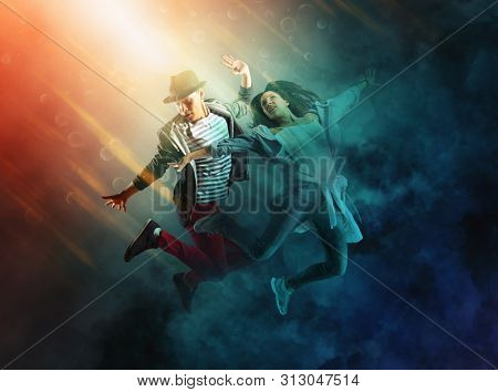 Hip-hop dance party. Couple hip-hop dancing on dark smoke background