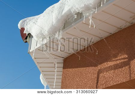 The Icicles Hanging From The Rim Of The Roof. The Spring Background Of Melting Ice And Snow In The S