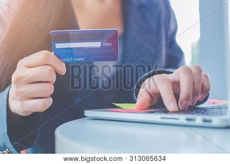 Business Women Are Carrying Credit Cards And Using Laptop Computers To Order Products Online.