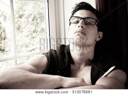 Portait Of Good Looking Young Latino Man With Spectacles, Sitting In Window