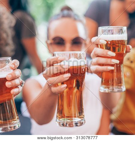 Happy group of best friends drinking light beer - Friendship concept with young female friends enjoying time and having genuine fun at outdoor nature ambient
