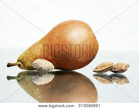 Still Life With Ripe Pear And Salted Almonds In Their Nutshells Against  High Key Background With Am