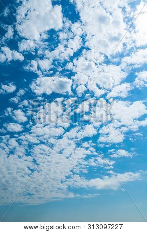 Blue dramatic sky background - white dramatic colorful clouds lit by sunlight. Vast sky landscape panoramic scene, white clouds in the sky, sky landscape scene