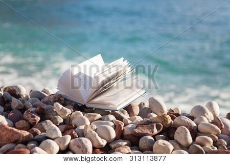 Book On Sea Beach. Concept Of Reading Paper Book, Relaxation In Holidays, Enjoying Summer Vacation.