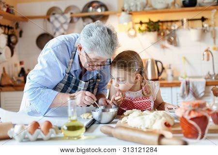 Family Is Cooking In Cozy Kitchen At Home. Grandmother And Child Are Making Italian Food And Meal. S