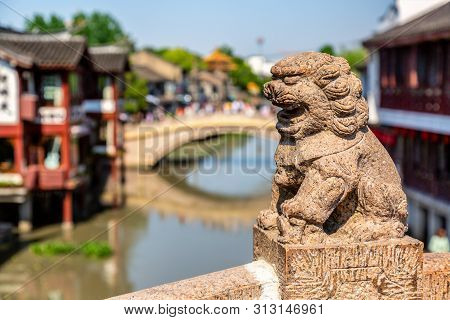 Qibao Old Town In Shanghai, China. Stone Statue On Brick Bridge Over The River In Qibao.