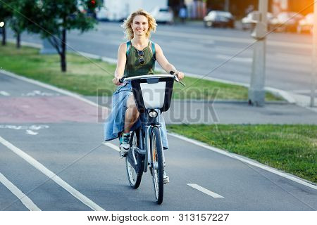 Photo Of Young Blonde In Long Denim Skirt Sitting On Bike On Road In City On Summer Day. Lensflare E