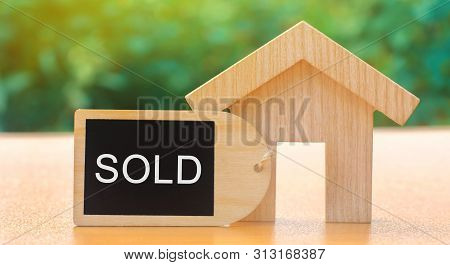 A Miniature Wooden House And Inscription Sold. The Concept Of Selling A Home Or Apartment. Property