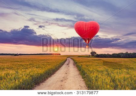 Red Hot Air Balloon In The Shape Of A Heart Above The Field With Rye And Road At Sunset Time.